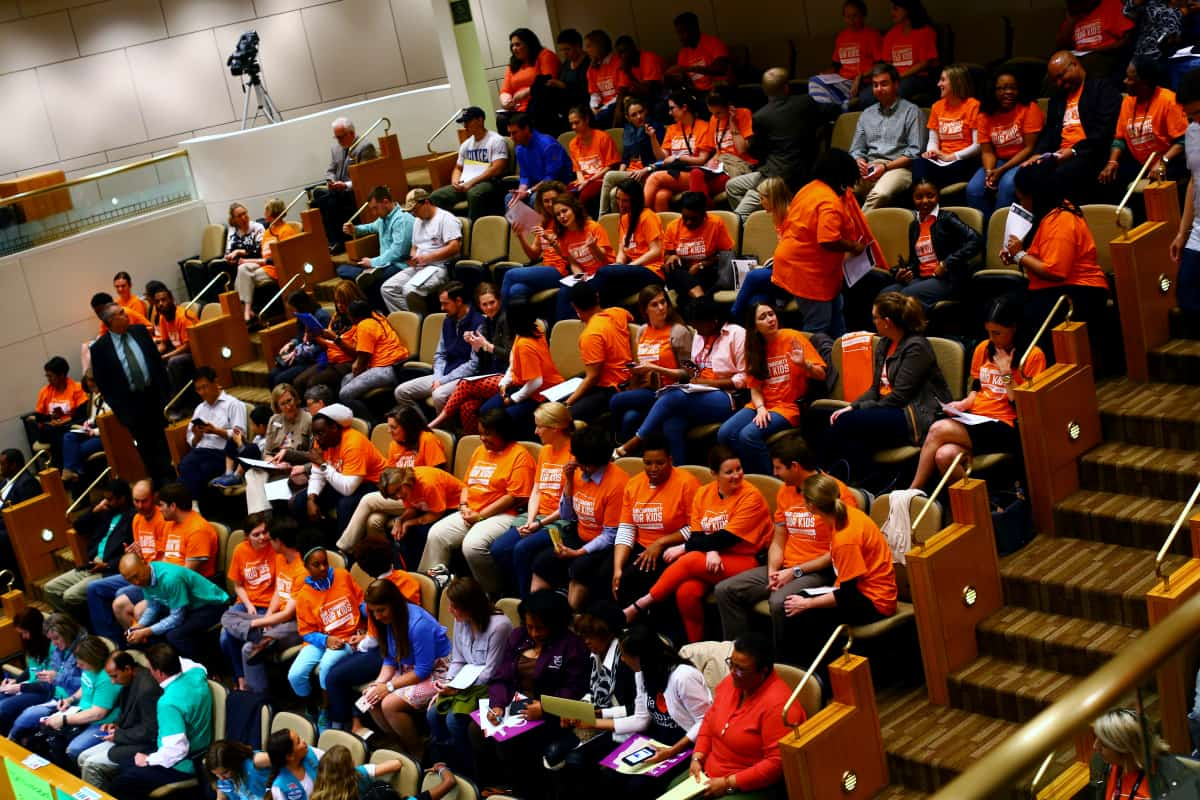 Charlotte, NC - Many of the audience members at a school board meeting show their allegiances through their shirts. Those in green want to keep their neighborhood schools, while the orange shirts support changes to the student assignment policies. Charlotte-Mecklenburg Schools is in the midst of a student assignment review, a process by which the school board evaluates and determines where students will attend school. Debate around this topic has consumed the school board, parents, and students in the nation's 17th largest district. Photo by Travis Dove for Scalawag