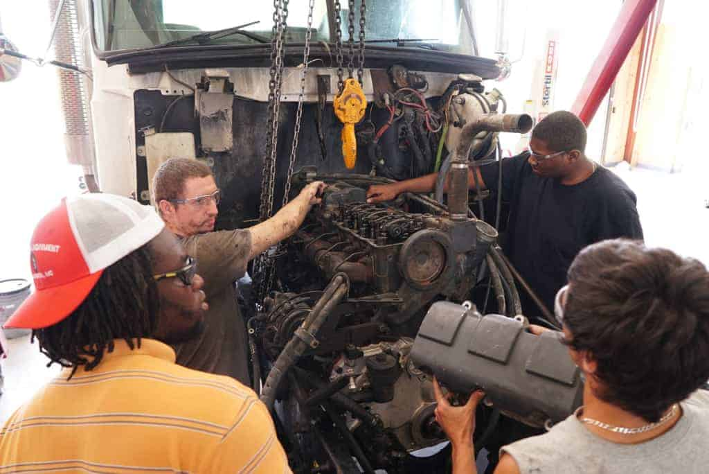 students work on a large Diesel engine